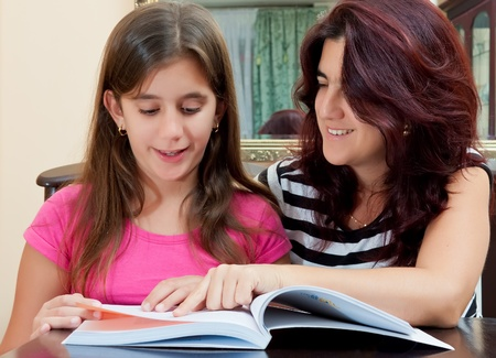 Beautiful hispanic girl and her young mother reading a book together or studying at home Stock Photo - 12902834