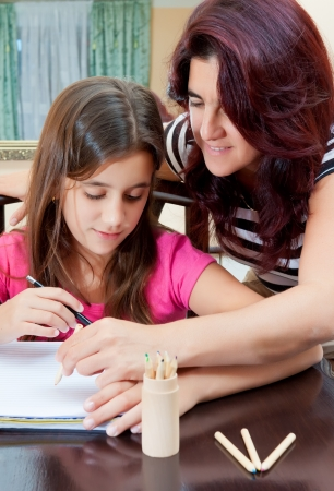 Beautiful hispanic girl and her young mother  studying at home photo
