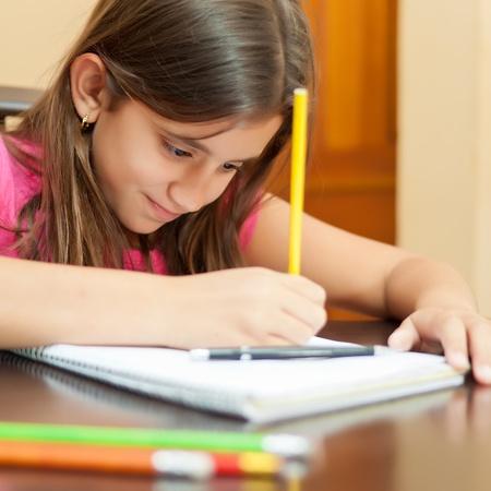 niños escribiendo: Retrato de una niña hispana hermosa que trabaja en su proyecto de arte en el hogar