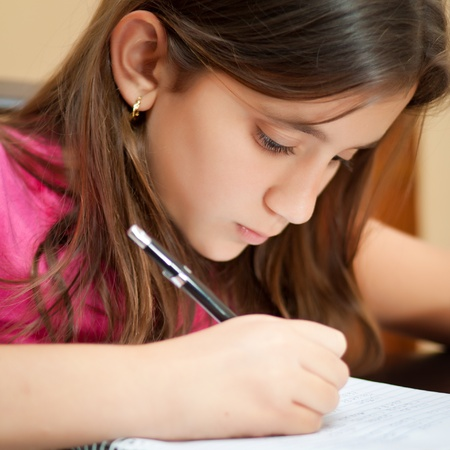 latin child: Close-up portrait of a cute hispanic girl writing on her school notebook