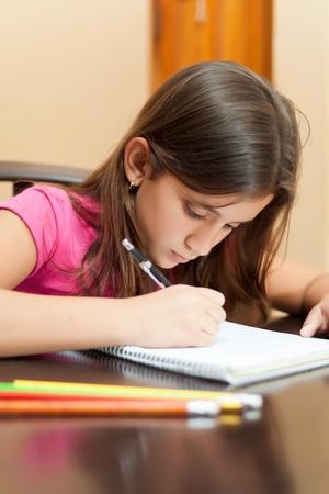 ni�os escribiendo: Retrato de una muchacha linda hispana que trabaja en su tarea escolar