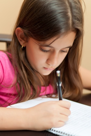 Vertical portrait of a cute hispanic girl writing on her school notebook photo