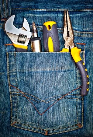 Varias herramientas en un bolsillo del pantalón de mezclilla Foto de archivo