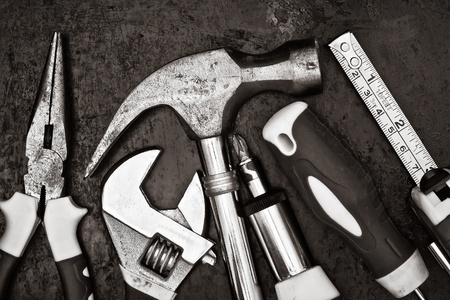 Black and white image of a set of tools on a textured metallic background photo