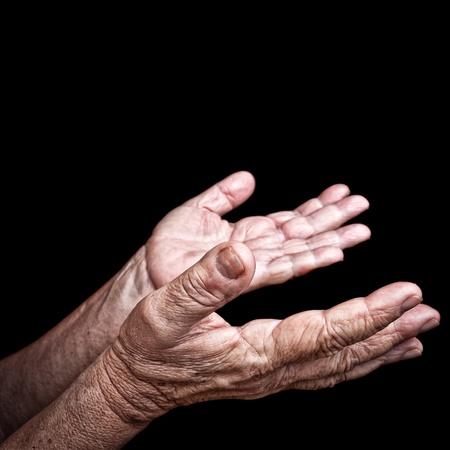 geloof hoop liefde: Gerimpelde oude handen bedelen geïsoleerd op een zwarte achtergrond Stockfoto