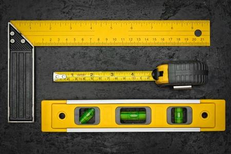 metro de medir: Conjunto de herramientas de medición en una textura de fondo negro metálico