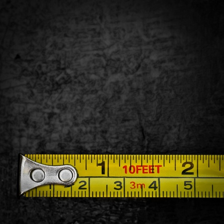 black metallic background: Yellow measuring tape on a textured black metallic background with space for text