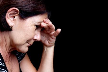 caras tristes: Retrato de una mujer mayor deprimida que sufre de estr�s o un fuerte dolor de cabeza aislado en negro Foto de archivo