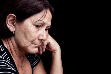seniors suffering painful illness: Portrait of a worried old woman with a sad expression isolated on black