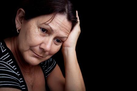 hoofdpijn: Portret van een zeer trieste en depressieve oudere vrouw die lijden aan stress of een sterke hoofdpijn geïsoleerd op zwart Stockfoto