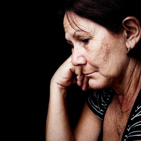 sad old woman: Retrato de una anciana triste, con una mirada nost�lgica tristeza aisladas en negro Foto de archivo