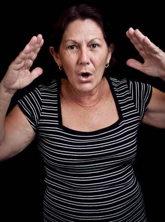 Portrait of an old woman screaming and gesturing with her hands isolated on a black background photo