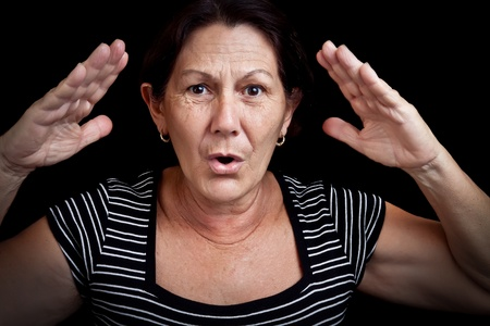Portrait of an old woman screaming and gesturing with her hands isolated on a black background Stock Photo - 12902922