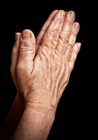praying together: Old wrinkled hands praying isolated on a black background