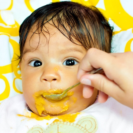Close-up portrait of a small hispanic baby girl eating her meal and making a mess photo