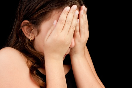 Emotional portrait of a girl crying and hiding her face isolated on black with space for text photo