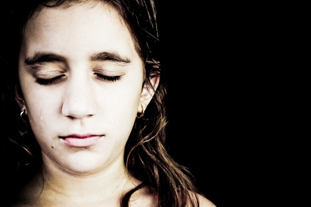 Dramatic portrait of a very sad girl crying isolated on black with space for text Stock Photo - 13162469