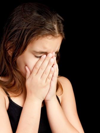 maltrato: Retrato emocional de una ni�a llorando y ocultando su rostro aislado en negro con espacio para texto