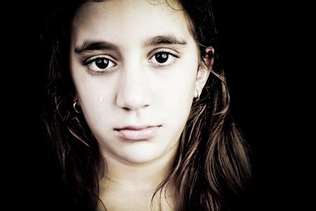 petite fille triste: Portrait dramatique d'une jeune fille très triste pleurer isolé sur fond noir avec espace pour le texte Banque d'images