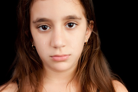 preteen: Very sad girl crying and looking at the camera isolated on black with space for text