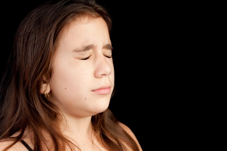 emotional pain: Dramatic portrait of a girl with a very sad face crying isolated on black with space for text Stock Photo