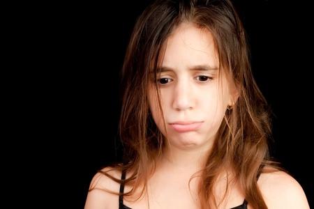 Sad melancholic girl crying isolated on a black background photo