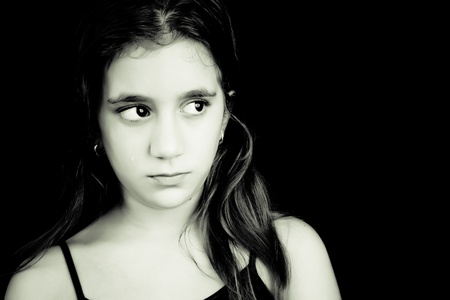 Monochrome portrait of a sad hispanic girl with tears on her face isolated on black photo