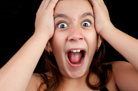 Portrait of a very surprised or scared girl screaming loudly with her hands on her head isolated on a black background photo