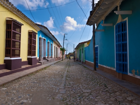 touristic: Narrow street sidelined by colorful houses in the colonial town of Trinidad in Cuba, a famous touristic landmark on the caribbean island