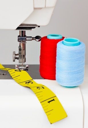 Sewing machine , reels with thread and a yellow measuring tape photo