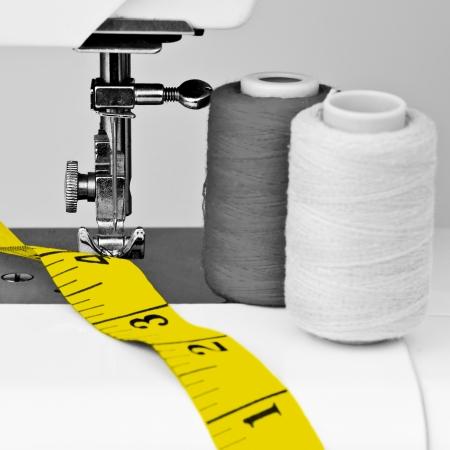 maquina de coser: Costura en blanco y negro de la m�quina y los carretes con hilo con una cinta m�trica en contraste de color amarillo Foto de archivo