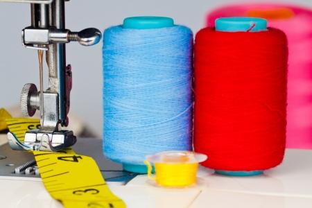 maquinas de coser: Máquina de coser, los carretes con hilo y una cinta métrica amarilla Foto de archivo