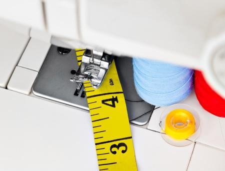 M�quina de coser, los carretes con hilo y una cinta m�trica amarilla Foto de archivo - 13338011