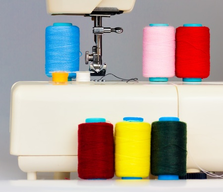 Sewing machine and a set of colorful reels with thread photo