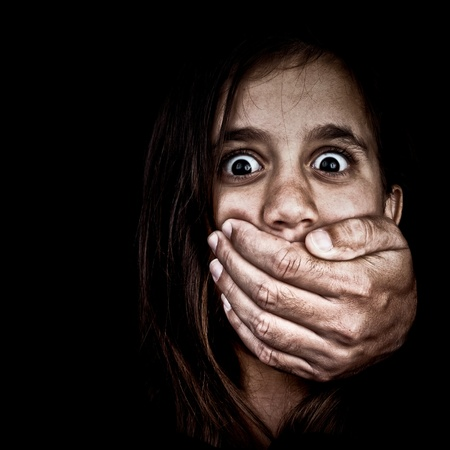 maltrato infantil: Retrato de una niña asustada siendo abusada por un hombre adulto que le cubre la boca con la mano sólo es visible la mano, el resto está oculto en las sombras