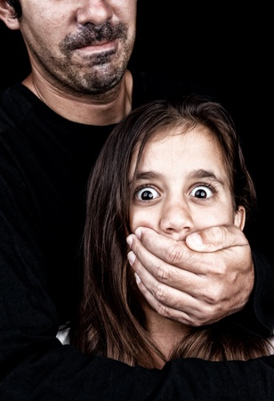 Scared girl being abused by an adult man who covers her mouth with his hand to prevent her from yelling photo