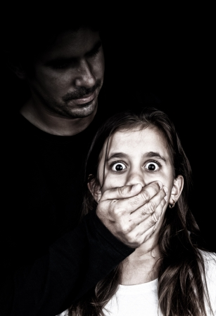 abused girl: Child abuse and harassment by an adult man with his face in the shadows