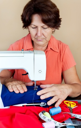 Hispanic woman working on a sewing machine with fabric and accesories on a table photo