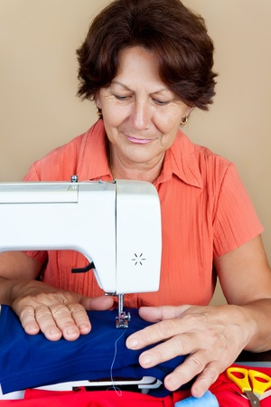 seamstress: Hispanic woman working on a sewing machine and smiling