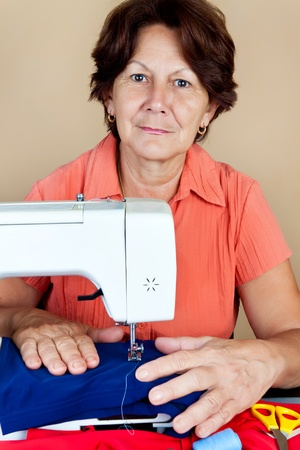 Hispanic woman working on a sewing machine and looking at the camera photo