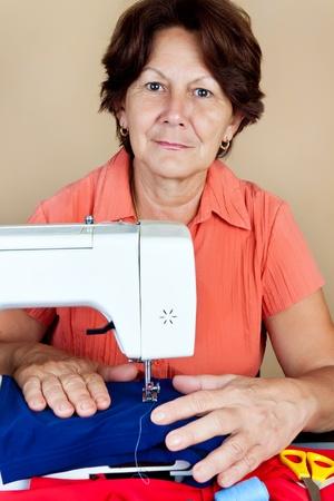 trabajando: Mujer hispana trabajando en una m�quina de coser y mirando a la c�mara