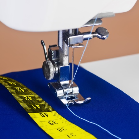 Close up of a sewing machine, thread and a yellow measuring tape in square format photo
