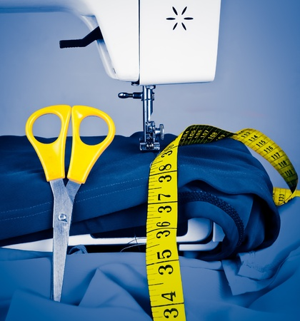 Sewing machine, measuring tape and scissors toned in blue shades with yellow details photo