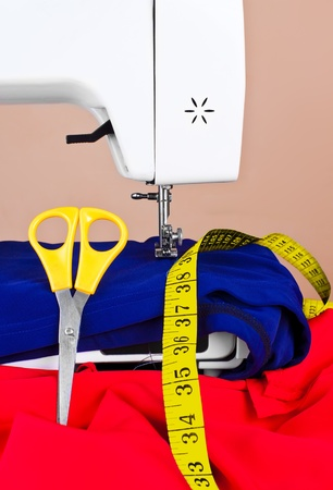Sewing machine, yellow measuring tape and scissors with red and blue fabric photo