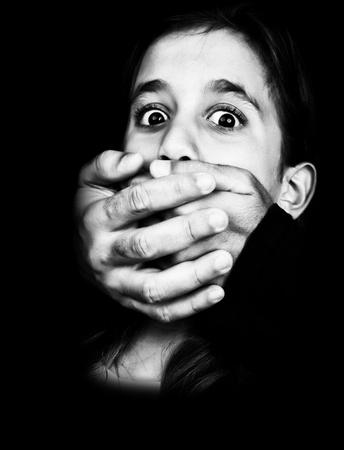 boca cerrada: Dramática imagen en blanco y negro de una niña víctima de abuso y silenciados con las dos manos que salen de un fondo negro y cubriendo su boca