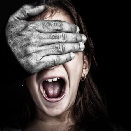 persiana: Primo piano di una ragazza abusato da un adulto con una mano pelosa desaturated coprendosi gli occhi, mentre lei urla Archivio Fotografico