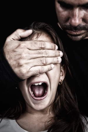Girl being abused  by an adult man who has a hand covering her eyes while she screams photo