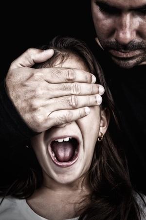 Meisje dat wordt misbruikt door een volwassen man die een hand voor haar ogen terwijl ze schreeuwt