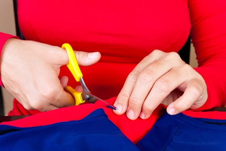 Close up of hands cutting a piece of fabric photo