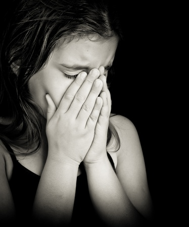 Emotional black and white portrait of a girl crying isolated on black with space for text photo